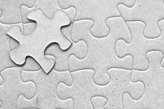 One floating piece of puzzle. Complete grey cardboard jigsaw puzzle with one floating piece on top Royalty Free Stock Photography