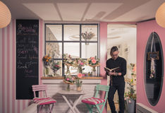One florist, flower shop outdoors, pink colors. One young man florist, flower shop outdoors, pink color, flowers Royalty Free Stock Photos