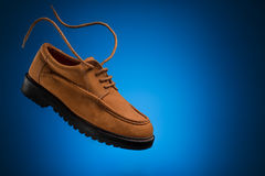 One flying leather boat shoes of wheat or brown nubuck with flying laces on a blue background Stock Photos