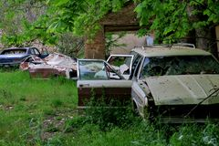In one of the forests in Europe the old battered and forgotten cars in the yard stock photos