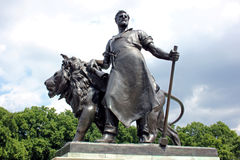 Bronze Statue Of Workman With Lion, Victoria Memorial, London. One of the four massive lions on the four sides of the Victoria Memorial, each with a human figure Stock Image