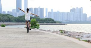 I can fly with my bike. One free woman riding bike with arms open on seaside stock video footage