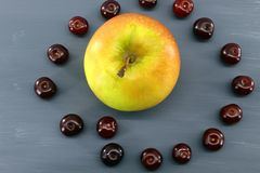 One fresh Apple surrounded by sixteen ripe cherries on a grey background stock photo
