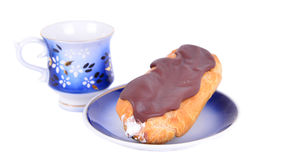 One fresh eclair on blue plate  with coffe cups Royalty Free Stock Photography