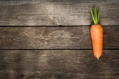 One fresh organic carrot on the wooden table. Copy space. One fresh organic carrot on the wooden table. Top view. Copy space Stock Photo