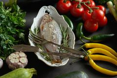 Fresh raw dorada fish in a white dish with a set of vegetables on a black table. One fresh raw dorada fish in a white dish with a set of vegetables on a black stock photos