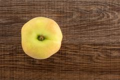 Fresh raw saturn peach on brown wood. One fresh ripe Saturn peach top view on brown wood background Royalty Free Stock Images