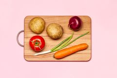 One Fresh Tomato And Green Onion Near Potatoes And Carrot. Healthy Eating. One Fresh Tomato And Green Onion Near Potatoes And Carrot On A Wooden Chopping Board Stock Images