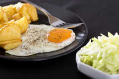 One fried egg with potatoes Stock Images