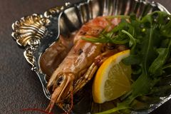 One fried large tiger shrimp head on with lemon and rukkola on ancient plate stock image