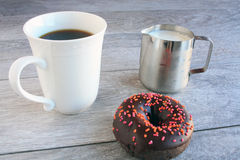 One frosted sprinkled dough nut with coffee and milk Royalty Free Stock Photos