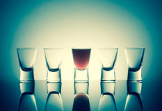 One full shot glass with alcohol drink with reflection next to t Stock Photo