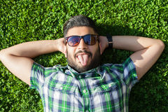 One funny fashion middle eastern man with beard and fashion hair style is resting on beautiful green grass day time. Stock Photo