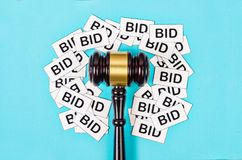 One gavel like those used on auctioning with the word bid. One gavel like those used on auctioning with the word bid on blue background Royalty Free Stock Images