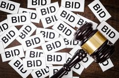 One gavel like those used on auctioning with the word bid. One gavel like those used on auctioning with the word bid on wooden background stock photo