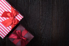 One gift box with an red big ribbon on old wooden dark brown bac Royalty Free Stock Photos