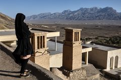 One girl in black chador looks at mountains, Yazd, Iran. Royalty Free Stock Images