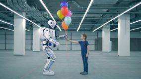 One girl gives balloons to a droid, side view. Little girl gifting balloons to a robot stock video footage