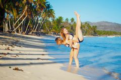 One girl holds the other girl on the back on a tropical seashore with tall palm trees royalty free stock image