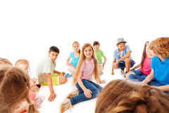 One girl in the large crowd sit smiling with mates Stock Photo