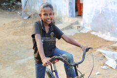 One girl is sitting on a bicycle and posing