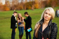 One girl student with friends on background royalty free stock photography