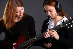 One girl teaches another to play the guitar Royalty Free Stock Image