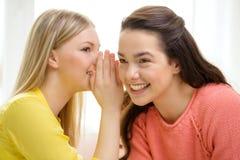 One girl telling another secret. Friendship, gossip and happiness concept - one girl telling another secret stock image