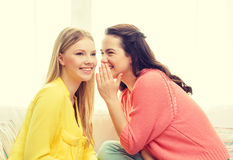 One girl telling another secret. Friendship, gossip and happiness concept - one girl telling another secret stock photos