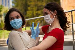 Girl try to hug another girl in protective masks and medical gloves, keep distance in quarantine in coronavirus COVID-19