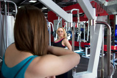 One girl watching another doing exercises in gym Royalty Free Stock Images