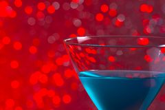 One glass blue cocktail on red background Royalty Free Stock Photo