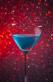 One glass blue cocktail on red tint light background Stock Photo