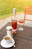 One glass and bottle of red or rose wine in vineyard with cup of coffee. Harvest time, cafe or picnic, fest theme Stock Photography