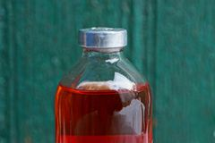 Glass closed medical bottle with red liquid medicine on green background royalty free stock images