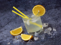 One glass of cold homemade lemonade with lemon slices, ice cubes and straws on dark background. Copy space Stock Image