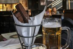 One glass of fresh light beer and salty snack, real scene in pub, bar. Oktoberfest, beer festival concept. One glass of fresh light beer and salty snack, real stock photography