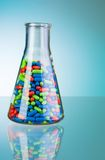 One glass full of color pills. Laboratory flask with green blue and red tablets and pills on blue Royalty Free Stock Image