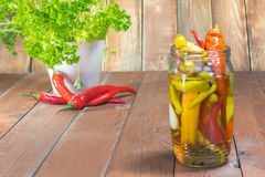 One Glass Jar Pickled Chilli Peppers with Fresh Chilli and Parsl Stock Photos