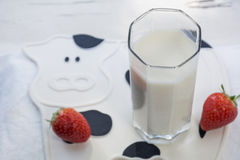 One glass of milk with several strawberries on the mat as cow Royalty Free Stock Image