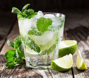 One glass of mojito cocktail with fresh lime. And mint on a wooden background Royalty Free Stock Images