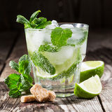 One glass of mojito cocktail with fresh lime. And mint on a wooden background Stock Images