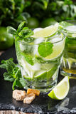 One glass of mojito cocktail with fresh lime. And mint on a wooden background Stock Photography