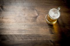One glass mug of beer. On wooden background stock photos