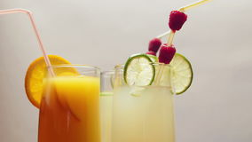 One glass of natural orange juice and two glasses of lemonade, rotating.  stock video footage