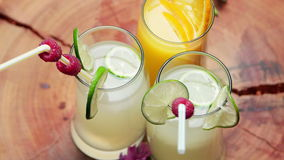 One glass of natural orange juice and two glasses of lemonade, rotating.  stock video