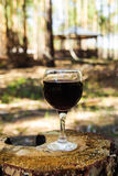 One glass with a red wine on a stump on a background of a summer forest. stock photography