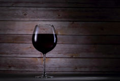 One glass with red wine. One glass with red with and wooden background Royalty Free Stock Photo