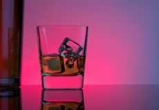 One glass of whiskey with ice cubes near bottle on table with reflection, lights disco atmosphere Stock Photography