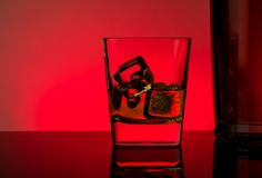 One glass of whiskey with ice cubes near bottle on table with reflection, red lights disco atmosphere Royalty Free Stock Images